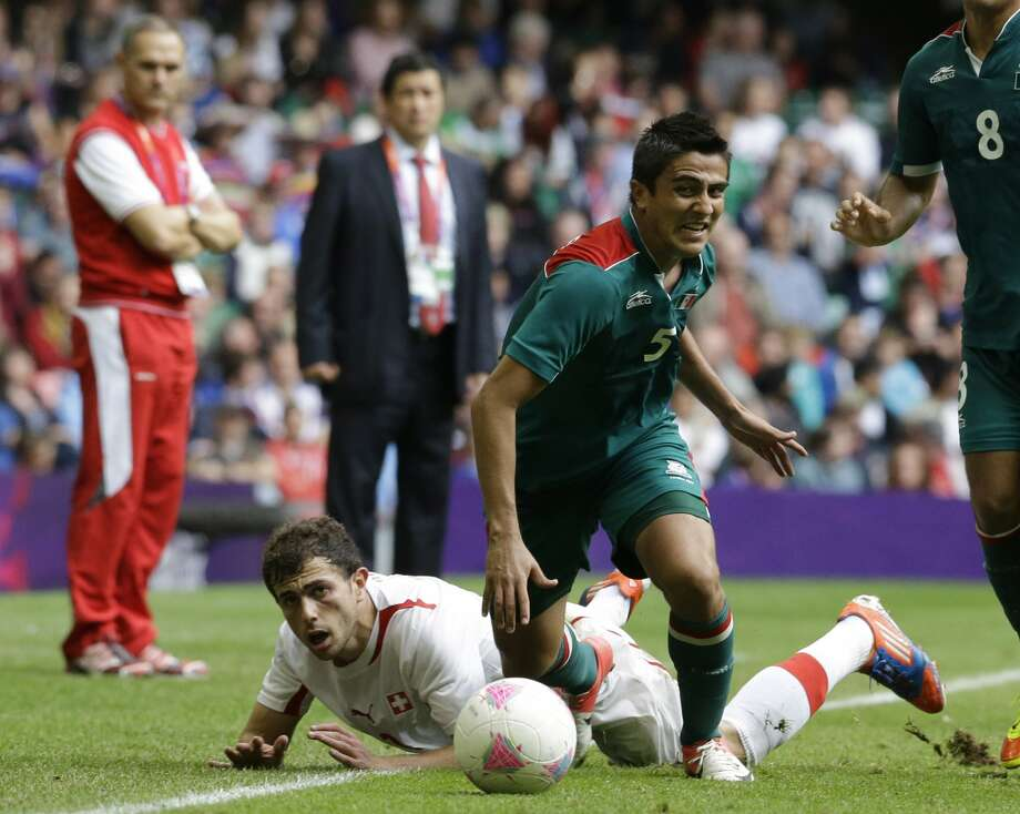 Mexico's Darvin Chavez, right, challenges for the ball with Switzerland's Admir Mehmedi, during the men's group B soccer match between Mexico and Switzerland, at the Millennium stadium in Cardiff, Wales, at the 2012 London Summer Olympics, Wednesday, Aug. 1, 2012. (Luca Bruno / Associated Press)