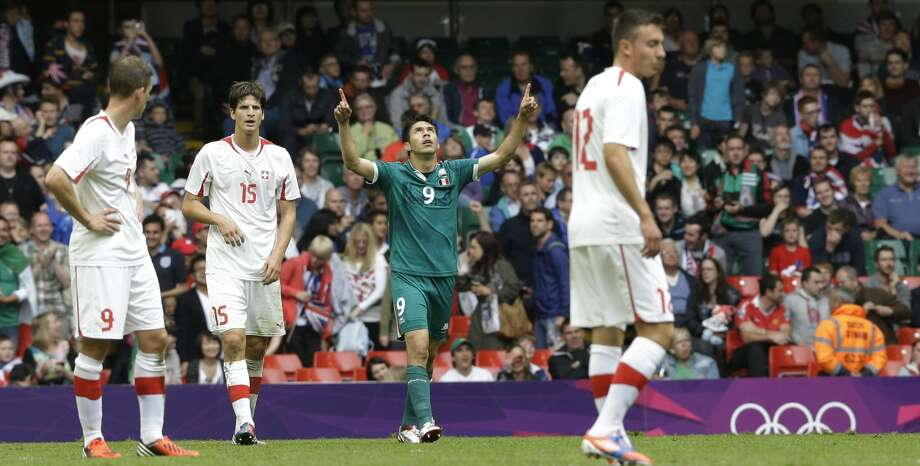 Mexico's Oribe Peralta, center, celebrates after scoring as Switzerland's Fabian Frei, left and his teammates Timm Klose (15), and Josip Drmic look on, during the men's group B soccer match between Mexico and Switzerland, at the Millennium stadium in Cardiff, Wales, at the 2012 London Summer Olympics, Wednesday, Aug. 1, 2012. (Luca Bruno / Associated Press)