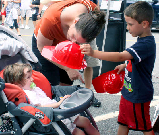 Johnny Gerardi, 2, of New Fairfield is presented with a firemen's hat by his brother, Nick, 6, as their mom, Theresa, looks on during the 45th annual New Milford Village Fair Days on the Village Green. July 28, 2012 Photo: Walter Kidd