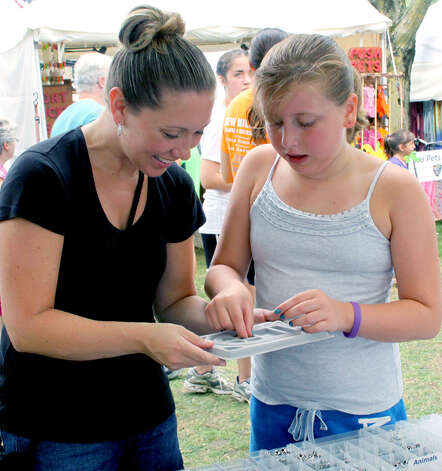 Samantha Guardino of New Milford selects charms for a bracelet with her mother, Stephanie, during the 45th annual New Milford Village Fair Days on the Village Green. July 28, 2012 Photo: Walter Kidd