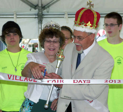 Village Fair Days royalty  Mary and Chris Prause, volunteers at the New Milford  Senior Center, perform the ribbon cutting last Friday as the first act of their reign as King and Queen of the Greater New Milford Chamber of Commerce's 45th annual Village Fair Days. Checking out the Prauses' style are, from left to right, volunteers Austin Hengel, Madison Meskill and Steve Malarkey. For more Village Fair Days photos, see Pages S6-7 and visit www.newmilfordspectrum.com. July 27, 2012 Photo: Trish Haldin