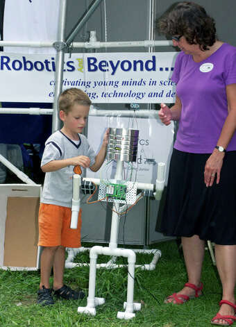 "Aaron Adamson, 5, of New Milford learns how ""Tim Can"" works from Marguerite Chayka at the Robotics and Beyond booth during the Greater New Milford Chamber of Commerce's 45th annual Village Fair Days. July 27, 2012 Photo: Trish Haldin"