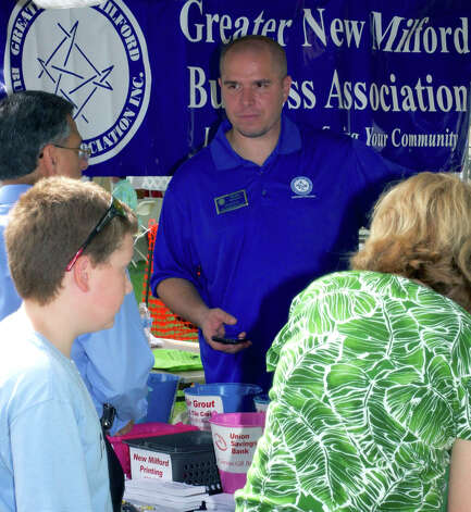 Vilem Fruhbauer in the Greater New Milford Business Association booth helps people fill out raffle tickets for a chance to receive free services from local businesses during the Greater New Milford Chamber of Commerce's 45th annual Village Fair Days. July 27, 2012 Photo: Trish Haldin