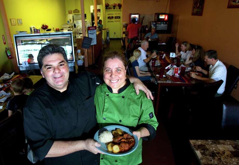 Owners Oscar Dasso and Ana Copello display their pork adobo. Photo: Cody Duty / © 2011 Houston Chronicle