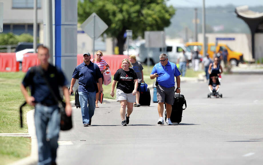 Travelers walk away from the San Antonio International Airport terminals during a bomb threatt on August 1, 2012. Photo: Tom Reel, Tom Reel / Express-News / ©2012 San Antono Express-News