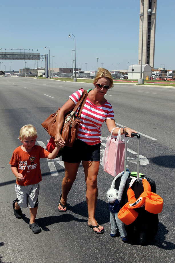 Michelle Heinanan walks away from the the San Antonio International Airport terminals with her son David during bomb threat on August 1, 2012. Photo: Tom Reel, Tom Reel / Express-News / ©2012 San Antono Express-News