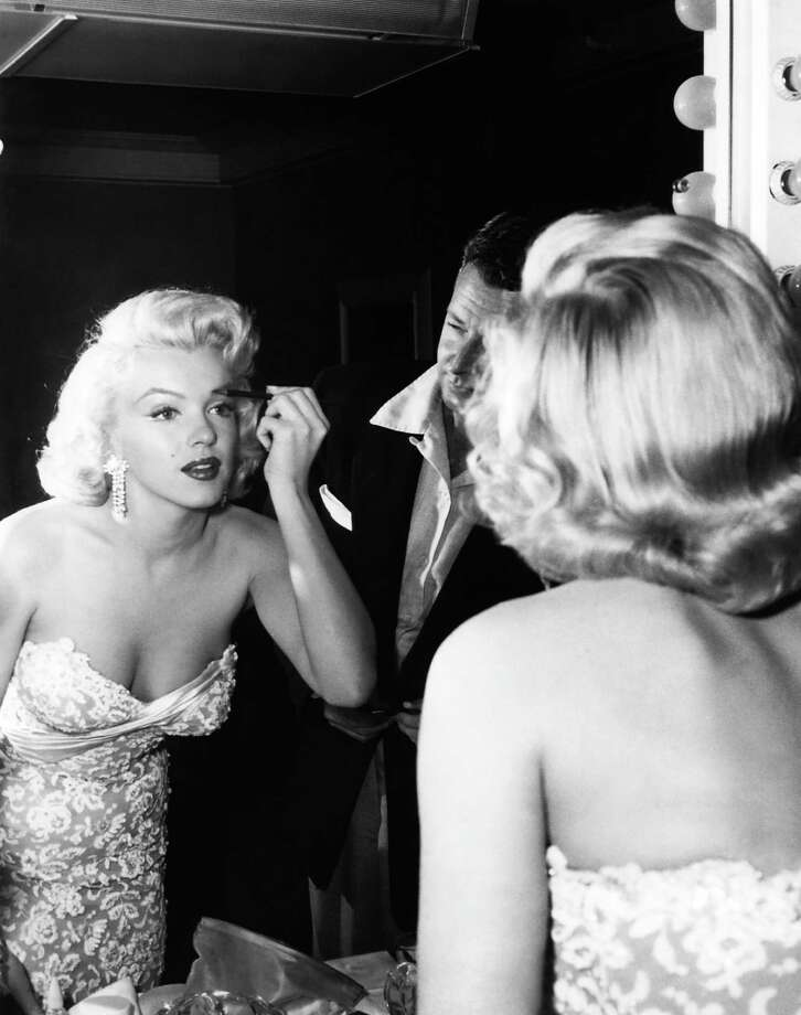 "Before heading to the premiere of ""How to Marry a Millonaire"" in 1953, Marilyn Monroe adds a finishing touch to her architectural eyebrows that she favored. Her favorite makeup man, Alan ""Whitey"" Snyder, looks on. Photo: Reprinted With Permission From T"