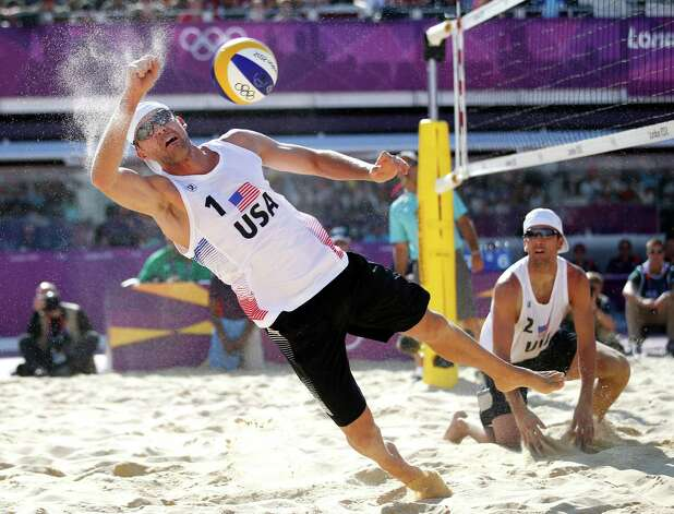 United States' Jacob Gibb, left, goes after the ball as Sean Rosenthal looks on during a beach volleyball match against Latvia's Aleksandrs Samoilovs and Ruslans Sorokins at the 2012 Summer Olympics, London, Wednesday, Aug. 1, 2012. Photo: Jae C. Hong