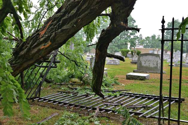A fallen tree crashed through a wrought iron fence at St. Mary's Cemetery along  McClellan Street in Schenectady following a brief thunderstorm on Wednesday, Aug. 1, 2012.   (John Carl D'Annibale / Times Union) Photo: John Carl D'Annibale