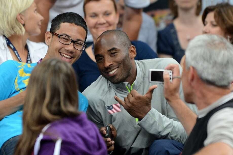 US basketball player Kobe Bryant (C) poses for a photograph as he attends the women's preliminary pool B volleyball match between the US and Brazil in the 2012 London Olympic Games in London on July 30, 2012. (Krill Kudryavtsev/Getty) (KIRILL KUDRYAVTSEV / AFP/Getty Images)