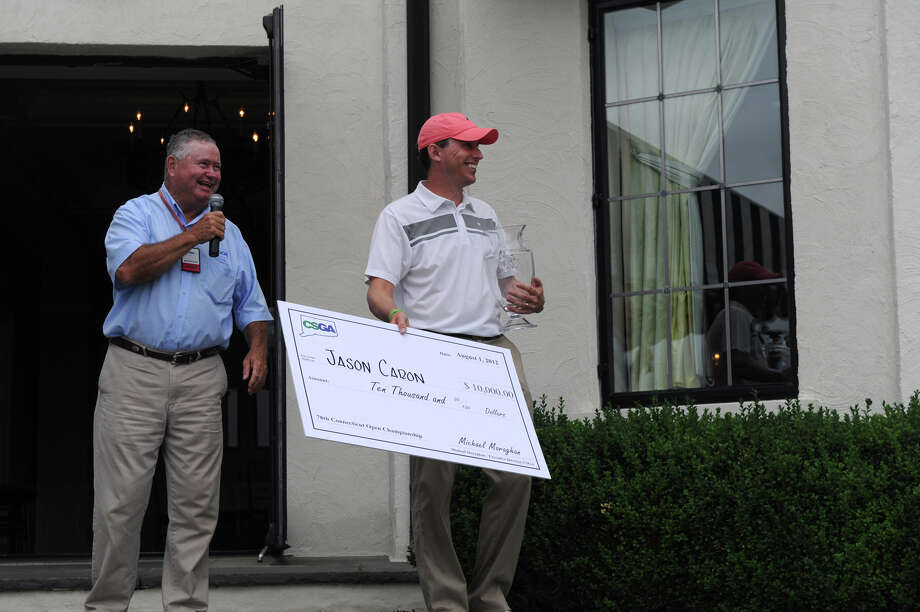 Jason Caron collects a $10,000 check from Malcolm McLachlan, Director of Rules & Competitions at the Connecticut State Golf Association after winning the 78th Connecticut Open Championship at Wee Burn Country Club in Darien, Conn., August 1, 2012. Photo: Keelin Daly / Stamford Advocate