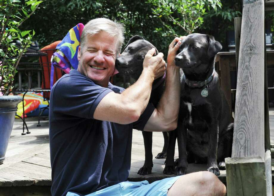 """RJ Kelly plays with his retrievers, Lulu, left, and Bella on his deck Monday, July 23, 2012.  RJ Kelly, who grew up in Darien but now lives in Wilton, recently snagged a role in the USA Network six-part miniseries """"Political Animals"""", which stars Sigourney Weaver and Ciarán Hinds. He plays the part of a Secret Service agent. Although the role is small, it is the first breakout after a long career in commercials, voiceovers, etc. Photo: Helen Neafsey / Greenwich Time"""