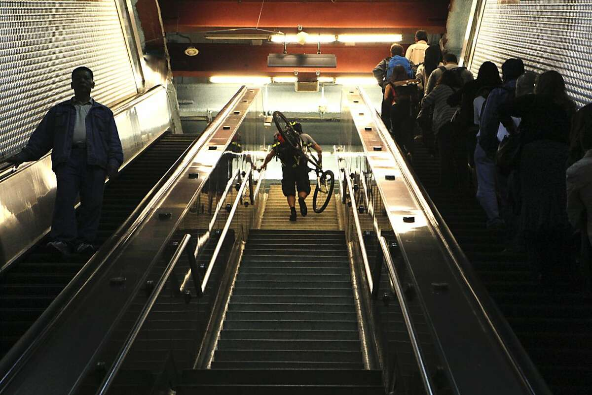 A commuter is seen carrying his bicycle in the Powell Street BART station on Tuesday, July 31, 2012, in San Francisco, Calif.