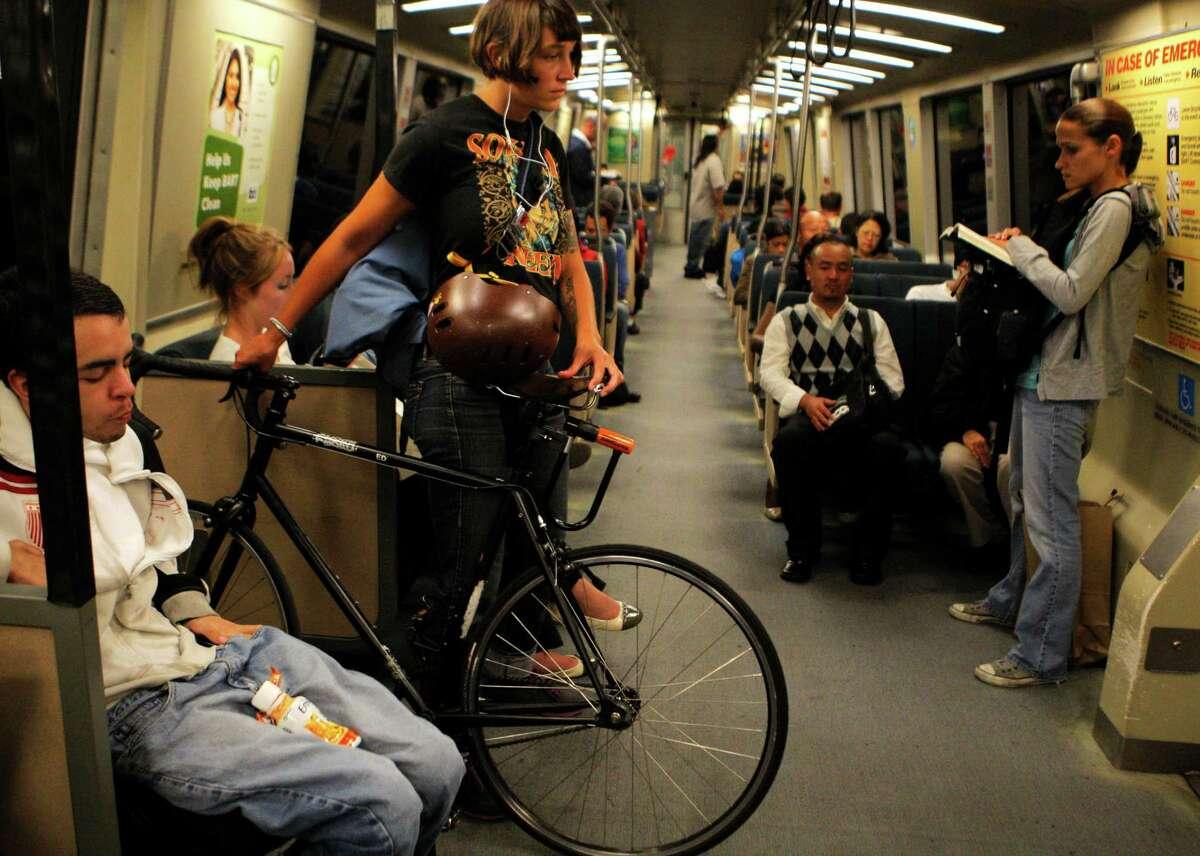 Commuter Evelyn Davis holds her bike on a BART ride through San Francisco.