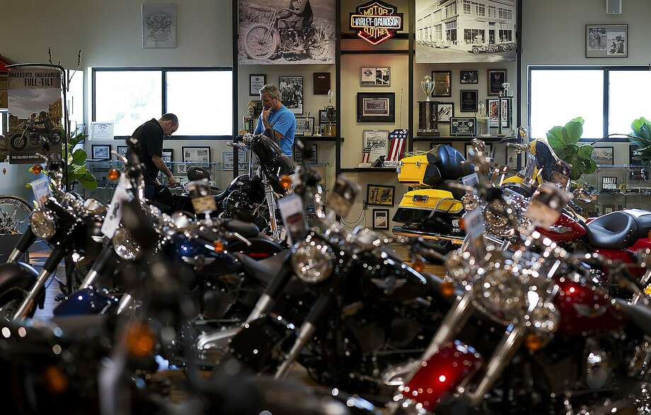 Employee Matt Lococo, left, helps a customer as they look over a Harley-Davidson Inc. CVO Street Glide model motorcycle at the Dudley Perkins Co. dealership in South San Francisco, California, U.S., on Wednesday, July 25, 2012. Photo: David Paul Morris, Bloomberg