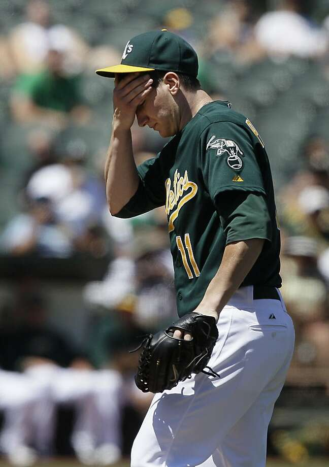 Oakland Athletics pitcher Jarrod Parker (11) wipes his face during the sixth inning of a baseball game against the Tampa Bay Rays in Oakland, Calif., Wednesday, Aug. 1, 2012. (AP Photo/Jeff Chiu) Photo: Jeff Chiu, Associated Press