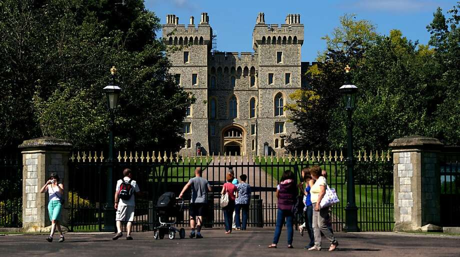 Tourists walk by the Windsor Castle, west of London, on Wednesday. Photo: Andrew Cowie, AFP/Getty Images