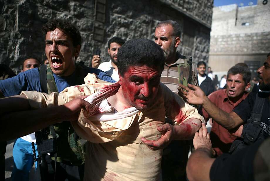 "====TURKEY OUT==== Rebel Free Syrian Army (FSA) fighters capture a policeman who the FSA allege is a ""Shabiha"" or pro-regime militiaman, on July 31, 2012, as the rebels overran a police station in Aleppo. A watchdog said that rebels killed 40 officers and seized three police stations during the pivotal battle for the commercial capital. AFP PHOTO/EMIN OZMEN/SABAH PRESSEMIN OZMEN/AFP/GettyImages Photo: Emin Ozmen, AFP/Getty Images"
