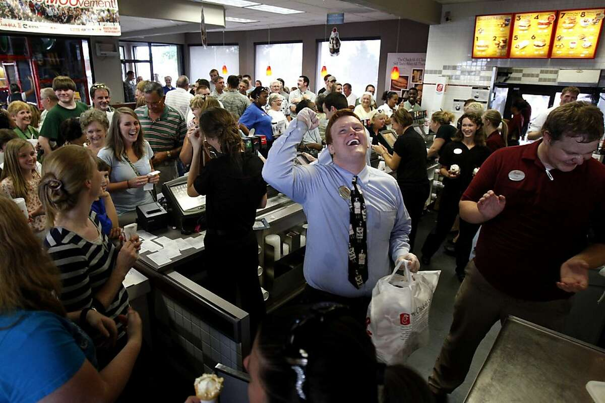 Chick-fil-A team member Dakota Bibbs, center, cheers as customers aid in his search for the owner of an order ready for pick-up in Southaven, Miss. Wednesday, Aug. 1, 2012,. Customers crowded into the Southaven restaurant and patiently waited up to an hour to receive their order in a display of support for the company's stance on marriage and family values. (AP Photo/The Commercial Appeal, Stan Carroll)