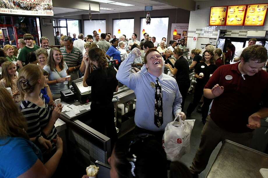 Chick-fil-A team member Dakota Bibbs, center, cheers as customers aid in his search for the owner of an order ready for pick-up in Southaven, Miss. Wednesday, Aug. 1, 2012,. Customers crowded into the Southaven restaurant and patiently waited up to an hour to receive their order in a display of support for the company's stance on marriage and family values. (AP Photo/The Commercial Appeal, Stan Carroll) Photo: Stan Carroll, Associated Press
