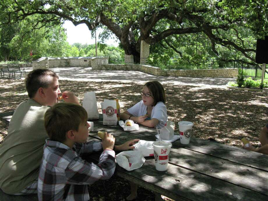 Noah Carroll (from left), Nicholas Dillard and Harlie Dillard enjoy treats near the tree in New Braunfels. Photo: Zeke MacCormack, San Antonio Express-News