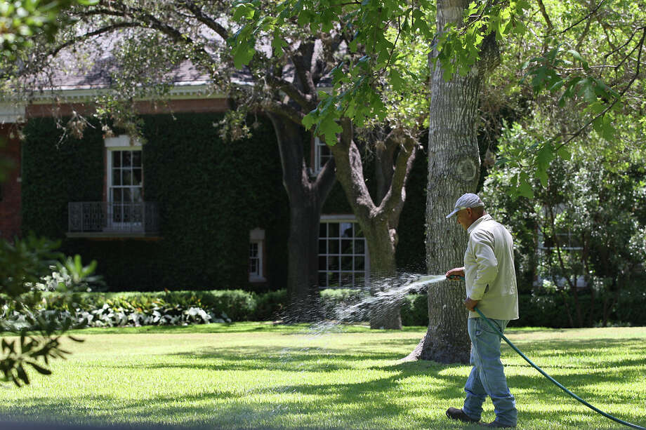 A worker hand waters the lawn at the Aliece Hollis residence at 720 Ivy Lane, Wednesday, Aug. 3, 2011. The residence is one of the top San Antonio Water Systems water user. JERRY LARA/glara@express-news.net Photo: JERRY LARA, San Antonio Express-News / SAN ANTONIO EXPRESS-NEWS
