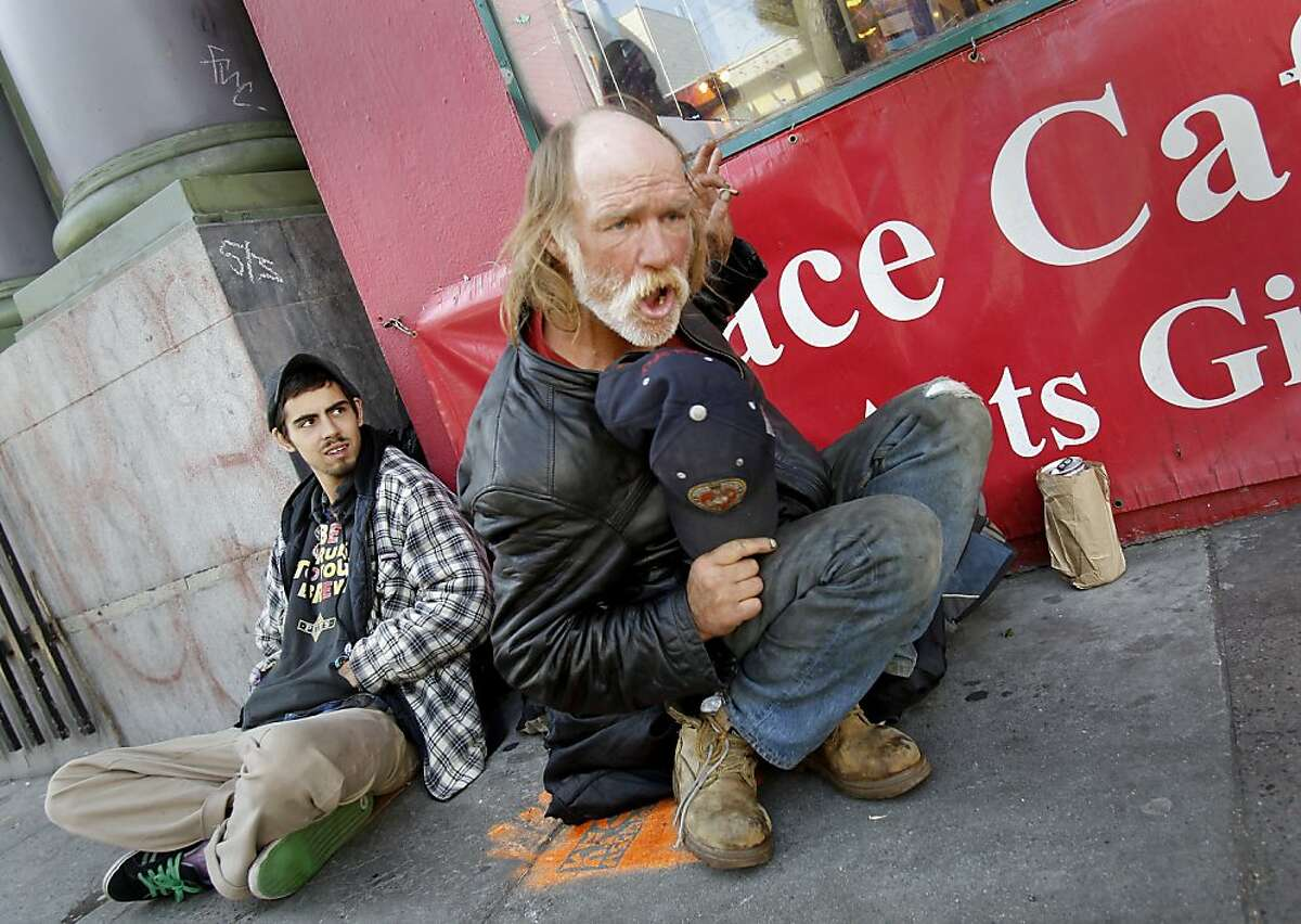 Lawrence Rosenberg (right), 54 years, enjoys an alcoholic beverage in front of the Red Victorian restaurant on Haight Street. Kyle Anderson is at left. San Francisco's controversial sit lie law, which makes it against the law to sit or lie on a city sidewalk, is being enforced exclusively in the Haight Ashbury neighborhood.