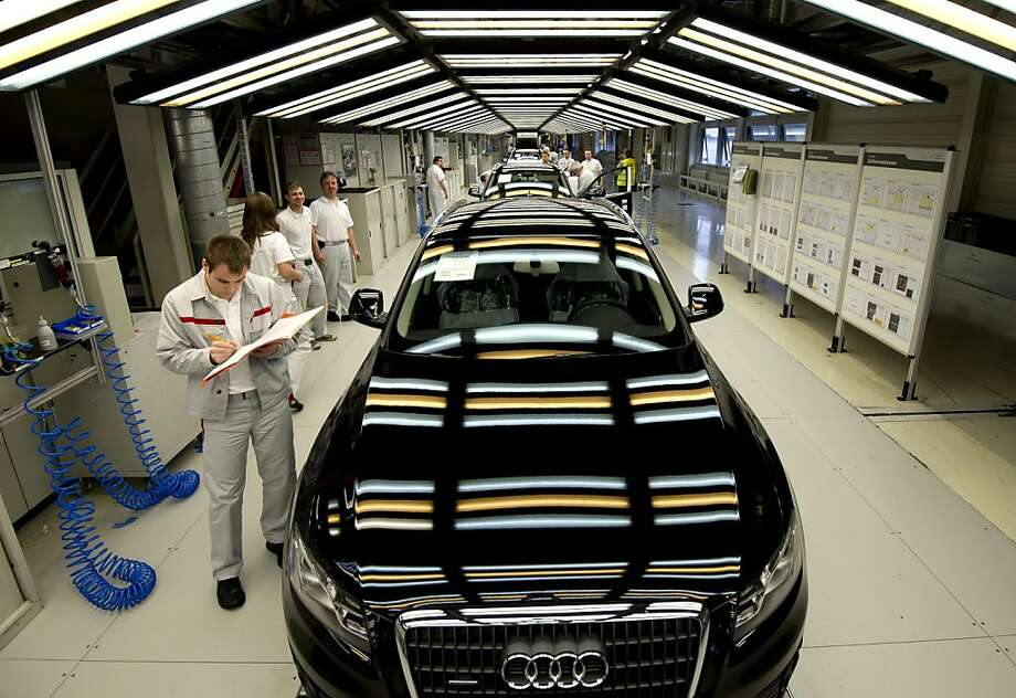 FILE - In this Feb. 29, 2012 file picture employees of Audi work at an assembly line of Audi Q3 cars in Ingolstadt, southern Germany. Audi, one of Volkswagen AG's luxury brands, saw sales jump 13 percent in June due to stronger demand in the company's home market of Germany as well as the US and China. The company sold 133,050 vehicles worldwide, up from 117,608 in June 2011. Sales rose 15 percent in Germany, 26 percent in the US and 20 percent in China. Audi CEO Rupert Stadler said Monday july 9, 2012, the company was on course to meet its goal of selling 1.4 million vehicles this year. The figures underlined the importance of China, where the company now gets a quarter of its sales, compared to just under 10 percent in the US. (AP Photo/dapd/Lukas Barth, File) Photo: Lukas Barth, Associated Press
