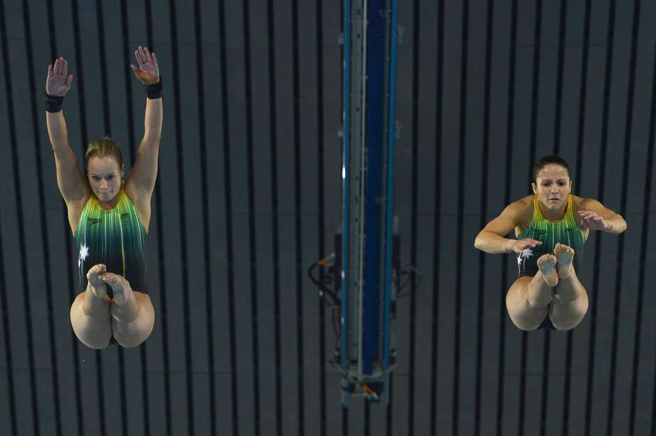 Hey, are my arms supposed to be like her's? Australia's Rachel Bugg and Australia's Loudy Wiggins put the un in synchronized diving on Tuesday.  (FABRICE COFFRINI/AFP/GettyImages) (AFP/Getty Images)
