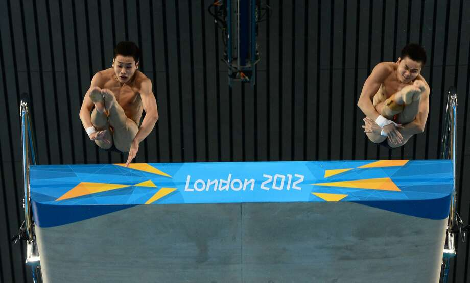 China's Cao Yuan, diving with Zhang Yanquan, motions for someone to get out of the pool. Nice to know that such a considerate young man won gold.  (CHRISTOPHE SIMON/AFP/GettyImages) (AFP/Getty Images)