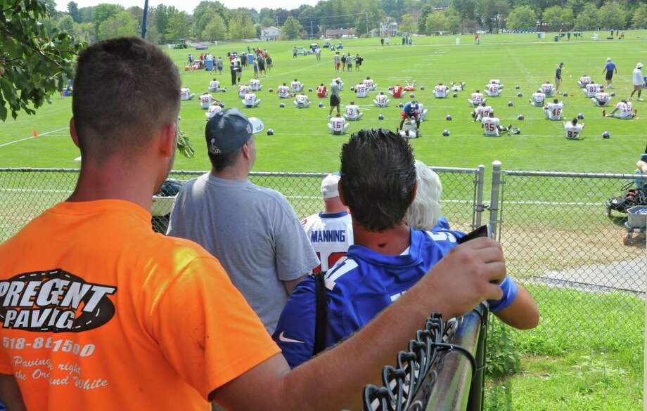 Fans sit on a hill to watch the New York Giants Training Camp Wednesday, August 1, 2012 in Albany, N.Y. (Lori Van Buren / Times Union) Photo: Lori Van Buren