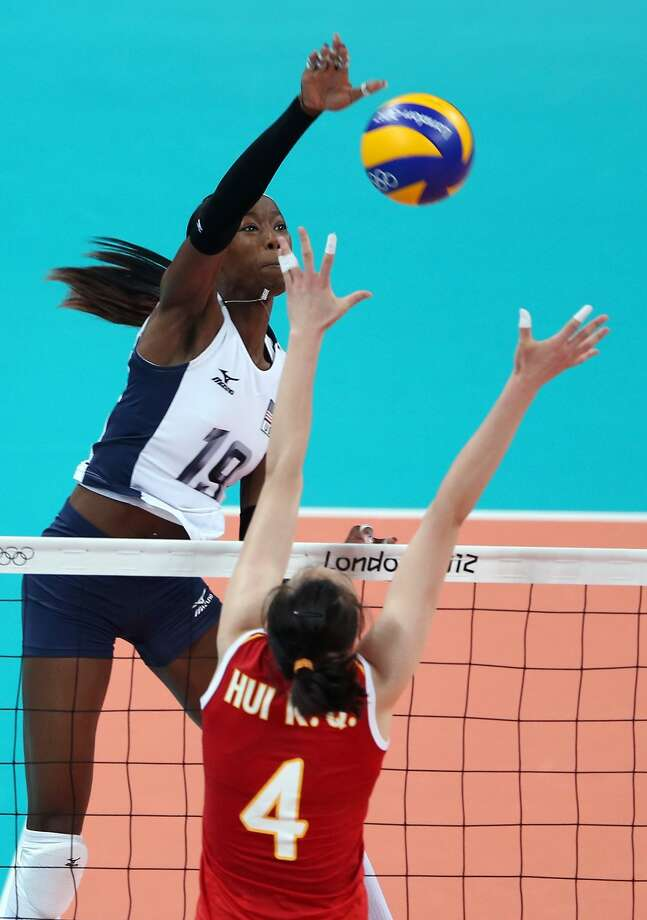 Team USA's Destinee Hooker spikes the ball over Chinese blocker Hui Ruoqi during a three-set victory Wednesday. (Elsa / Getty Images)