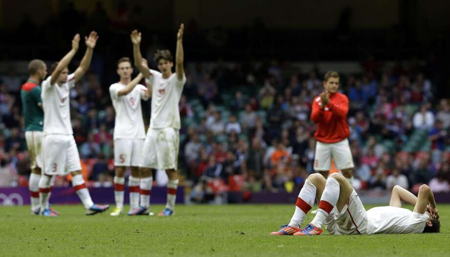Switzerland's Admir Mehmedi lies on the ground as his teammates acknowledge supporters at the end the men's group B soccer match between Mexico and Switzerland, at the Millennium stadium in Cardiff, Wales, at the 2012 London Summer Olympics, Wednesday, Aug. 1, 2012. Mexico won 1-0 and advances to the quarterfinals. (Luca Bruno / Associated Press)