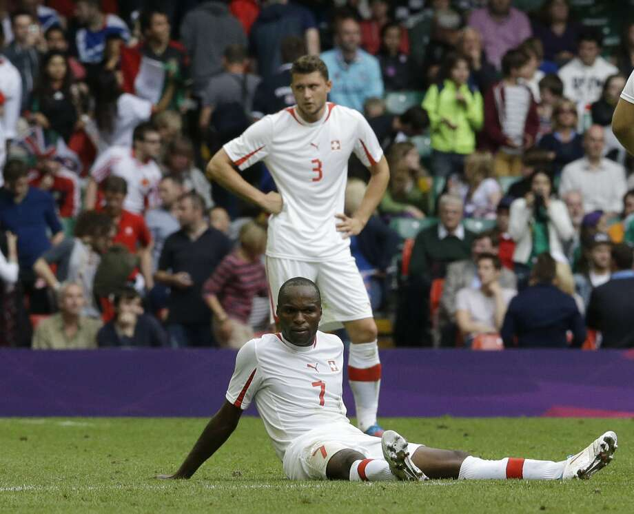 Switzerland's Innocent Emeghara, on the ground, and his teammate Fabio Daprela react at the end the men's group B soccer match between Mexico and Switzerland, at the Millennium Stadium in Cardiff, Wales, at the 2012 London Summer Olympics, Wednesday, Aug. 1, 2012. Mexico won 1-0 and advances to the quarterfinals. (Luca Bruno / Associated Press)