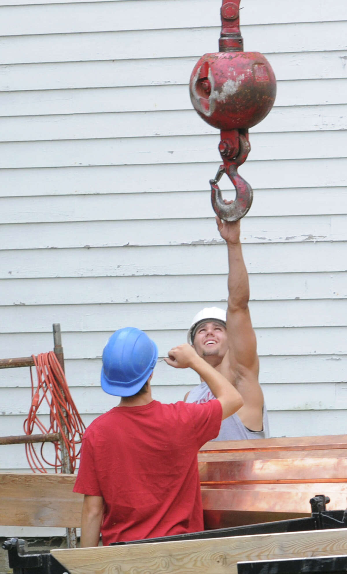 Jesse Tuttle, left, and Leo Lynch of Tuttle Construction get ready to hook a spire on a crane for the Rensselaerville Presbyterian church on Wednesday, August 1, 2012 in Rensselaerville, N.Y. The spire was lifted and placed on the steeple. (Lori Van Buren / Times Union)