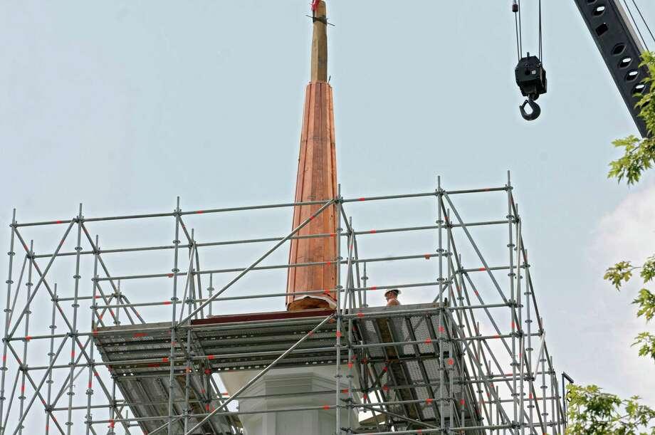 The spire of the Rensselaerville Presbyterian church is lifted and placed once again atop the steeple on Wednesday, August 1, 2012 in Rensselaerville, N.Y. (Lori Van Buren / Times Union) Photo: Lori Van Buren