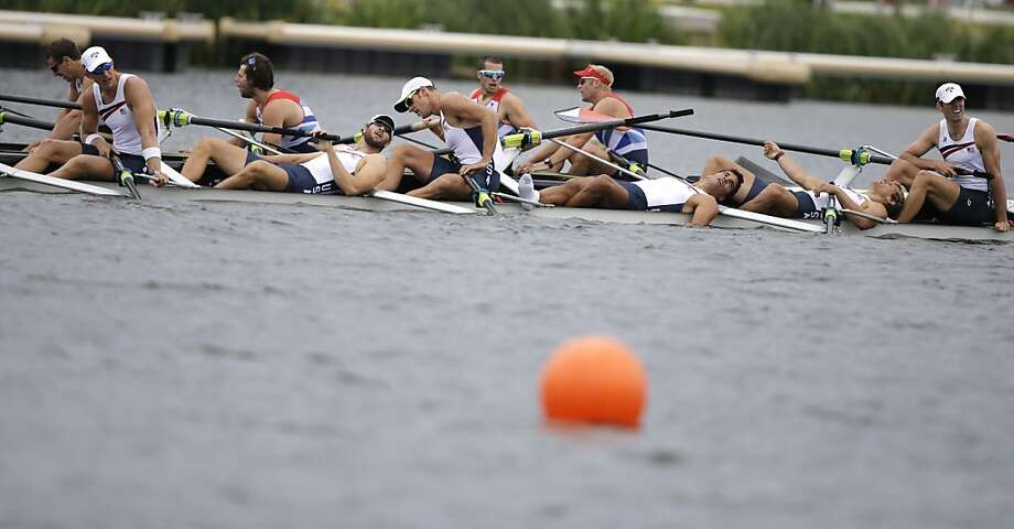 U.S. rowers lay on their boat after finishing fourth in the men's rowing eight final in Eton Dorney on Wednesday. Photo: Chris Carlson, Associated Press