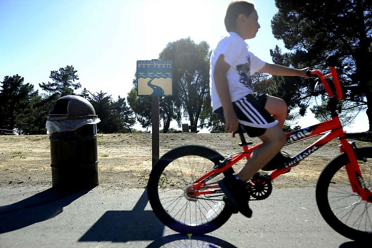 Angel Valencia(8yrs old) rides his bike past a sign for Bay Trails at Miller/Knox Regional Shoreline, Wednesday August 1st, 2012. Richmond got $700,000 from the Cosco Busan settlement and plans to use it to connect key portions of the Bay Trail between the Port, Point Richmond, Point San Pablo and Point Pinole.