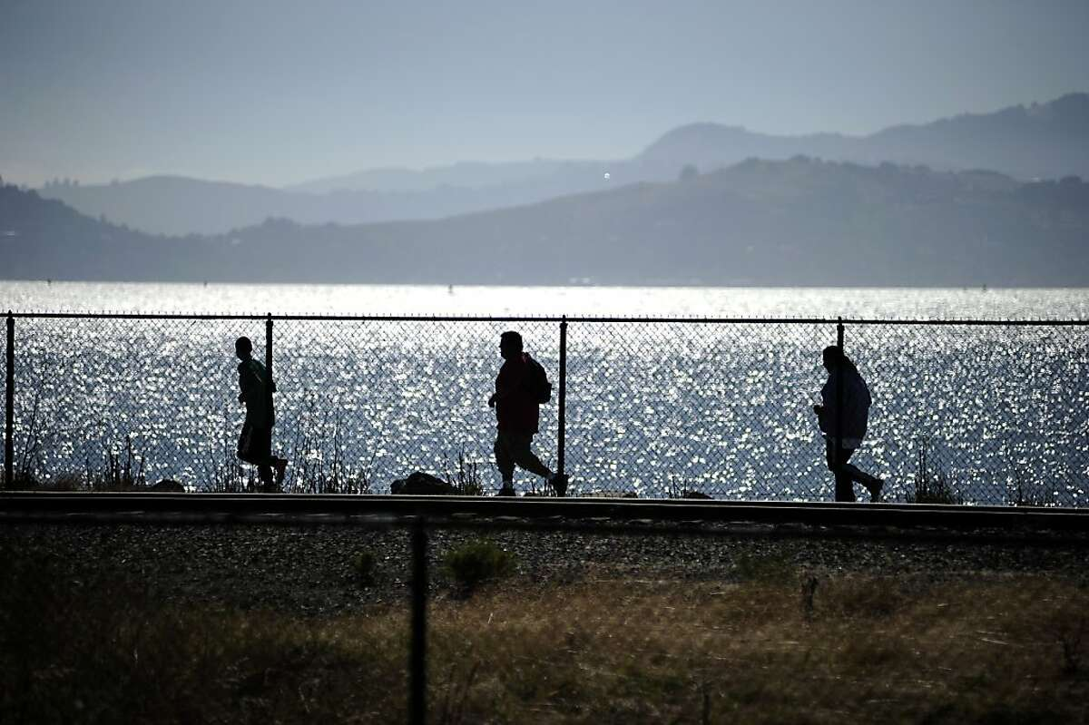 Visitors run along the shore line at Miller/Knox Regional Shoreline Park which Bay Trails runs through, Wednesday August 1st, 2012. Richmond got $700,000 from the Cosco Busan settlement and plans to use it to connect key portions of the Bay Trail between the Port, Point Richmond, Point San Pablo and Point Pinole.
