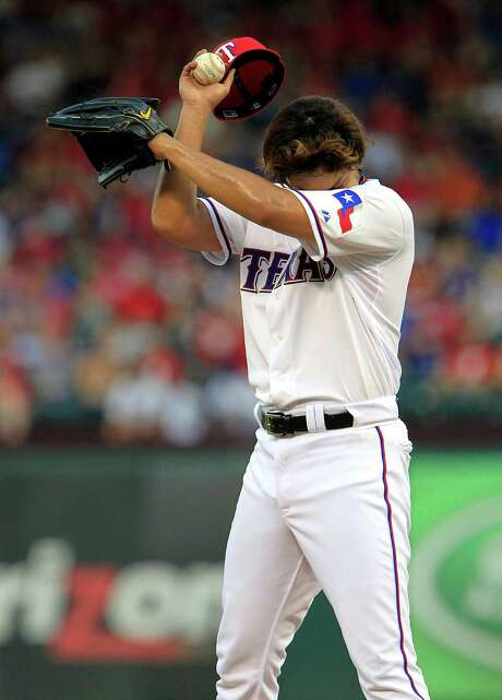 Yu Darvish tries to gather himself during a third inning in which the Rangers starter gave up six runs. Photo: John F. Rhodes, Associated Press / FR170608 AP