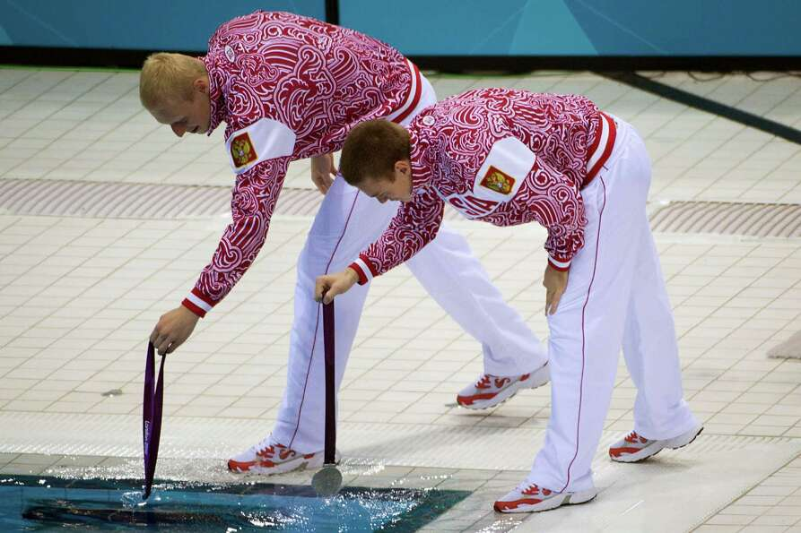 Ilya Zakharov and Evgeny Kuznetsova of Russia dip their medals in the pool after taking silver in th