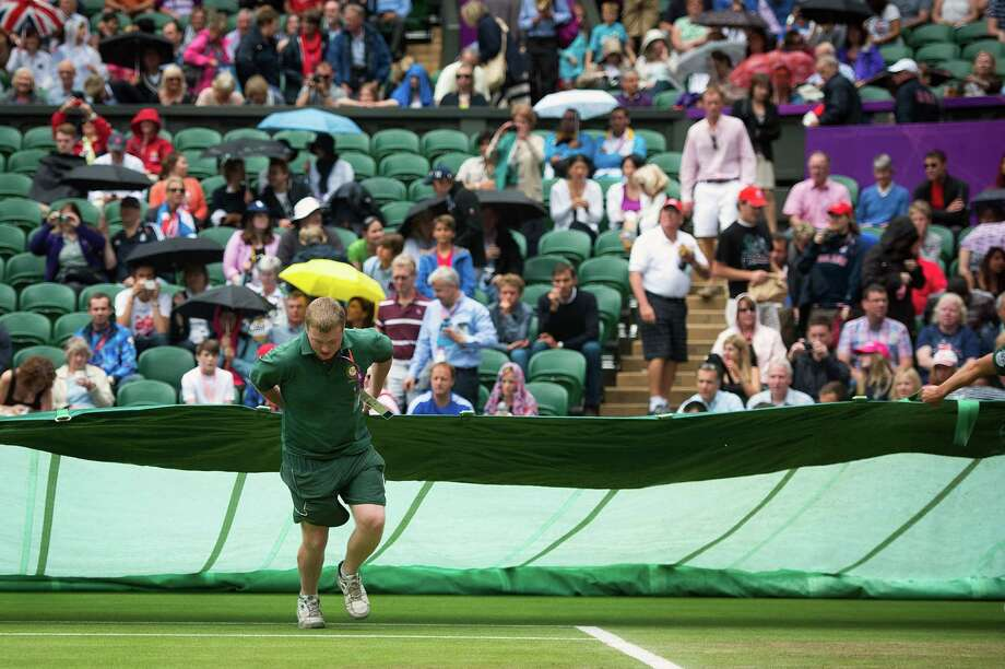 Workers cover the playing surface with a tarp as rain suspends play in the tennis competition at Wimbledon during the 2012 London Olympics on Wednesday, Aug. 1, 2012. Photo: Smiley N. Pool, Houston Chronicle / © 2012  Houston Chronicle