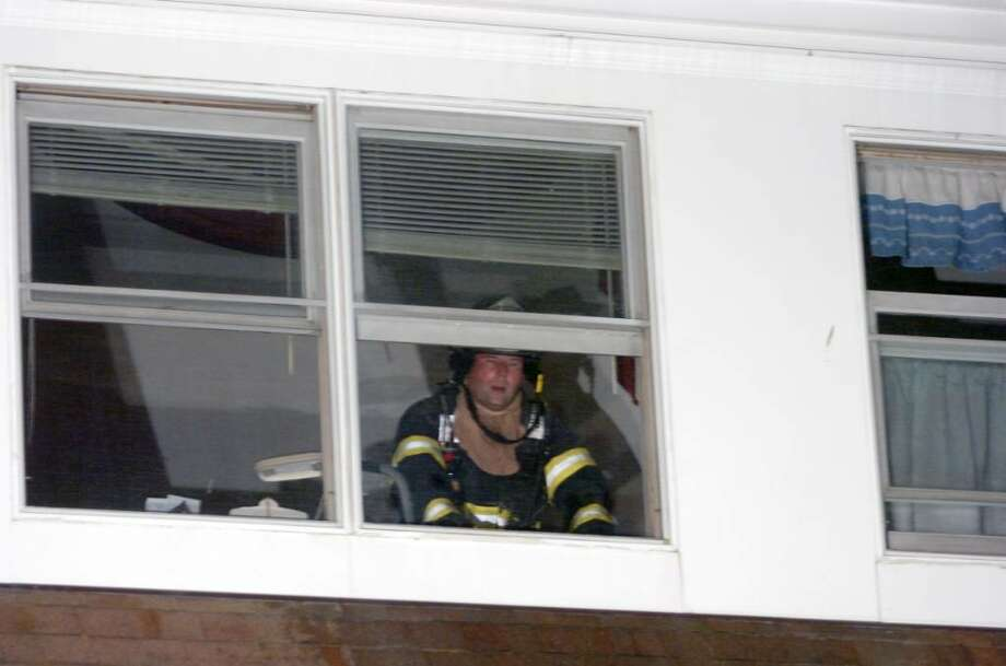 A firefighter shouts down from a second story window on the scene of a structure fire at the Old Greenwich Gables condominium complex at 51 Forest Avenue late Tuesday, Dec. 1, 2009. The fire spread through several units displacing numerous residents and causing extensive damage to exterior of the building; the battle to contain it went well into the night. Photo: Keelin Daly / Greenwich Time