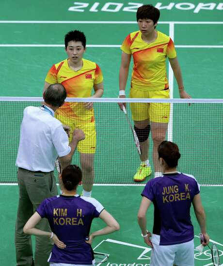 An official talks to the Chinese, top, during a match against the South Koreans in which both teams, later disqualified, were trying to lose. Photo: Saurabh Das / AP