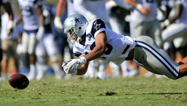 Dallas Cowboys wide receiver Dez Bryant cannot hold on as the offense executes a play during NFL football training camp, Wednesday, Aug. 1, 2012, in Oxnard, Calif. (AP Photo/Gus Ruelas) Photo: Gus Ruelas, Associated Press / FR157633 AP