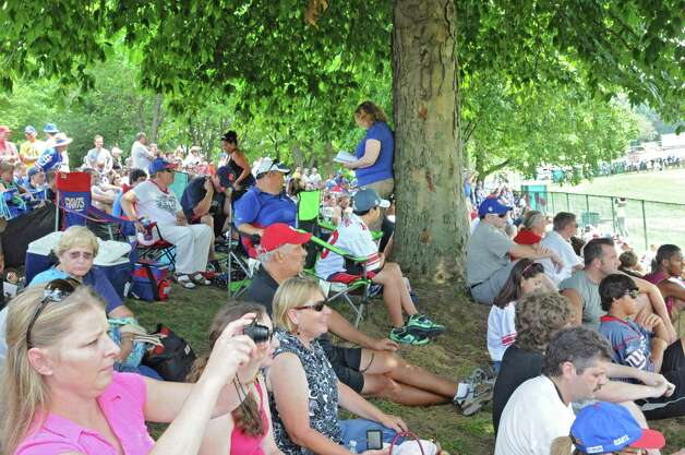 Fans sit on a hill to watch the New York Giants Training Camp Wednesday, August 1, 2012 in Albany, N.Y. One woman decides to read against a tree.(Lori Van Buren / Times Union) Photo: Lori Van Buren