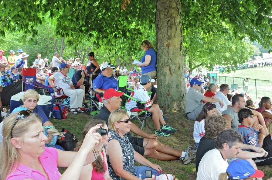 Fans sit on a hill to watch the New York Giants Training Camp Wednesday, August 1, 2012 in Albany, N