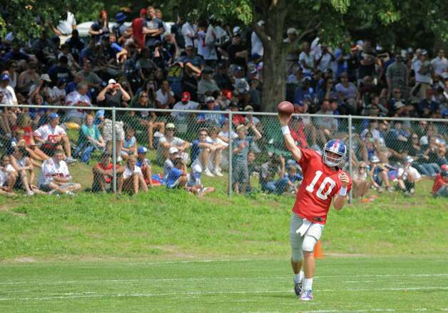 Fans sitting on a hill watch quarterback Eli Manning pass the ball during New York Giants Training Camp Wednesday, August 1, 2012 in Albany, N.Y. (Lori Van Buren / Times Union) Photo: Lori Van Buren