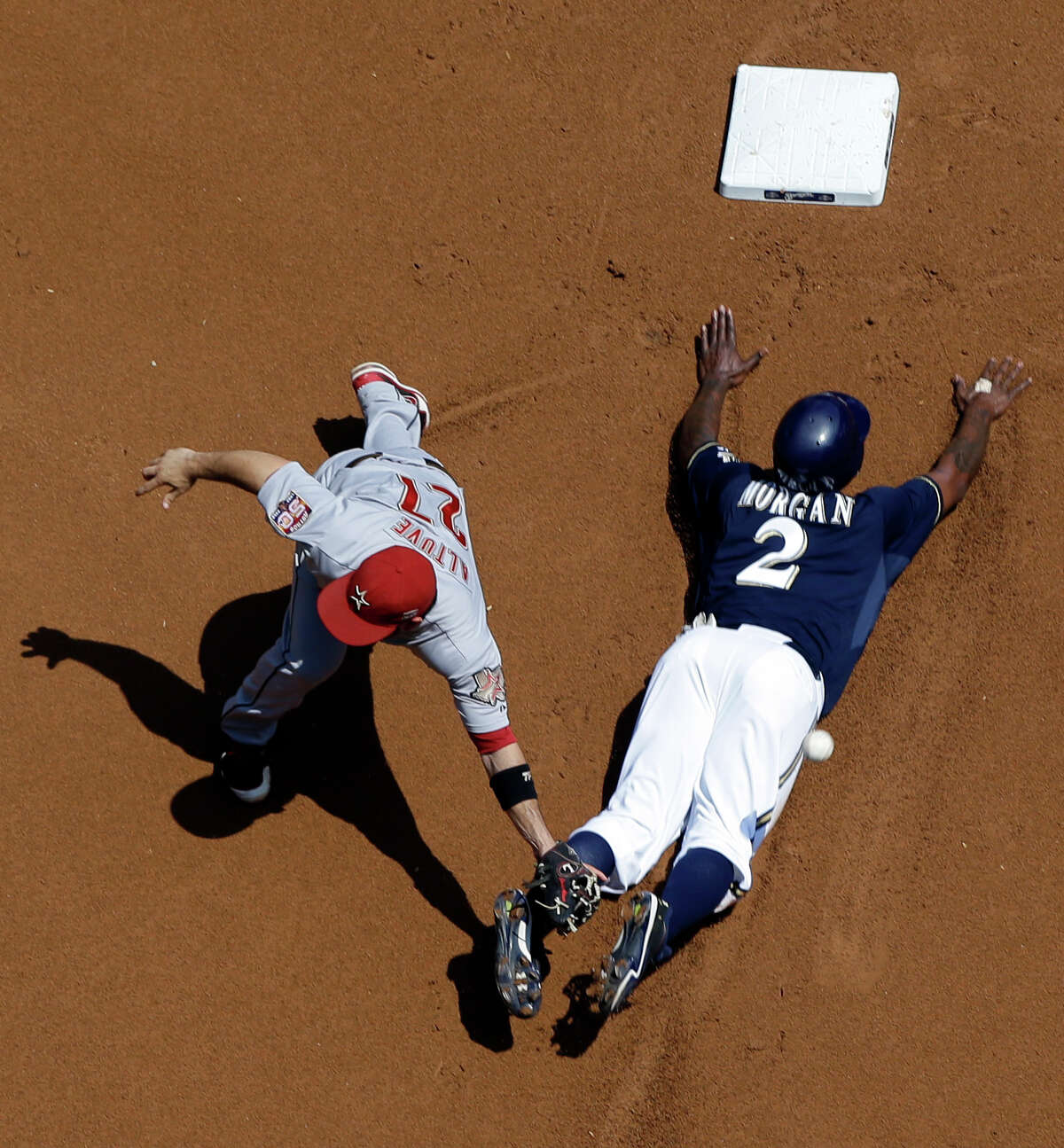 The throw gets away from Jose Altuve on a first-inning steal of second by the Brewers' Nyjer Morgan.