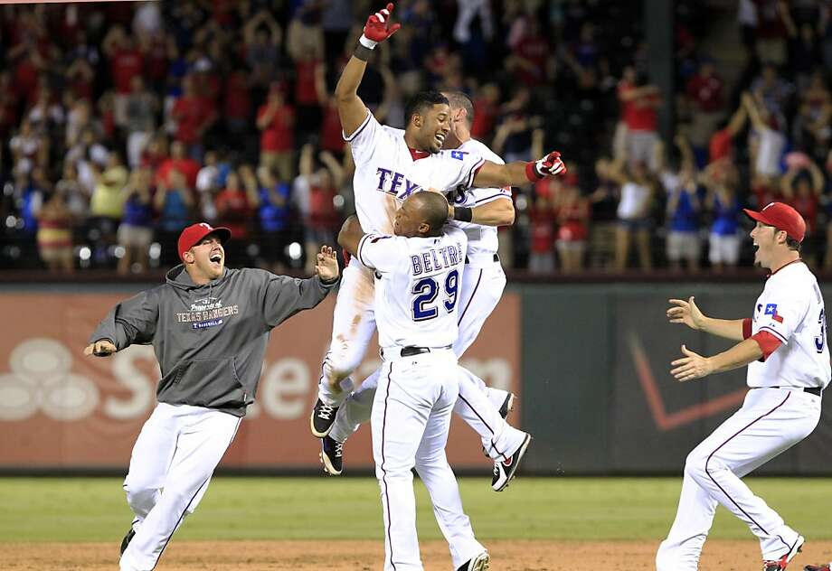 Texas Rangers shortstop Elvis Andrus (hands up) celebrates with teammates Robbie Ross, left, Adrian Beltre (29), Texas Rangers designated hitter Michael Young (behind Andrus) and Joe Nathan, right, after hitting a clutch two-run single that drove in the winning runs in the team's 11-10 victory in ten innings over the Los Angeles Angels on Wednesday, Aug. 1, 2012, in Arlington, Texas. (AP Photo/John F. Rhodes) Photo: John F. Rhodes, Associated Press